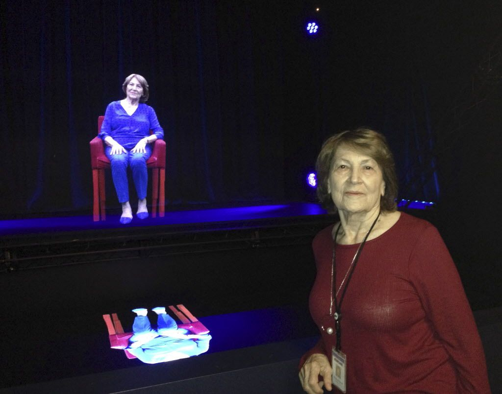 In this Oct. 20, 2017 photo, Holocaust survivor Fritzie Fritzshall poses for a portrait in front of her 3D hologram at the Illinois Holocaust Museum in Skokie, Ill. Fritzshall is one of 13 Holocaust survivors who tell their stories through holographic ima