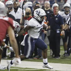 Utah State running back Calvin Tyler Jr., right, carries the ball while pressured by Washington State defensive back Tanner Moku, obscured, during the first half of an NCAA college football game Saturday, Sept. 4, 2021, in Pullman, Wash.