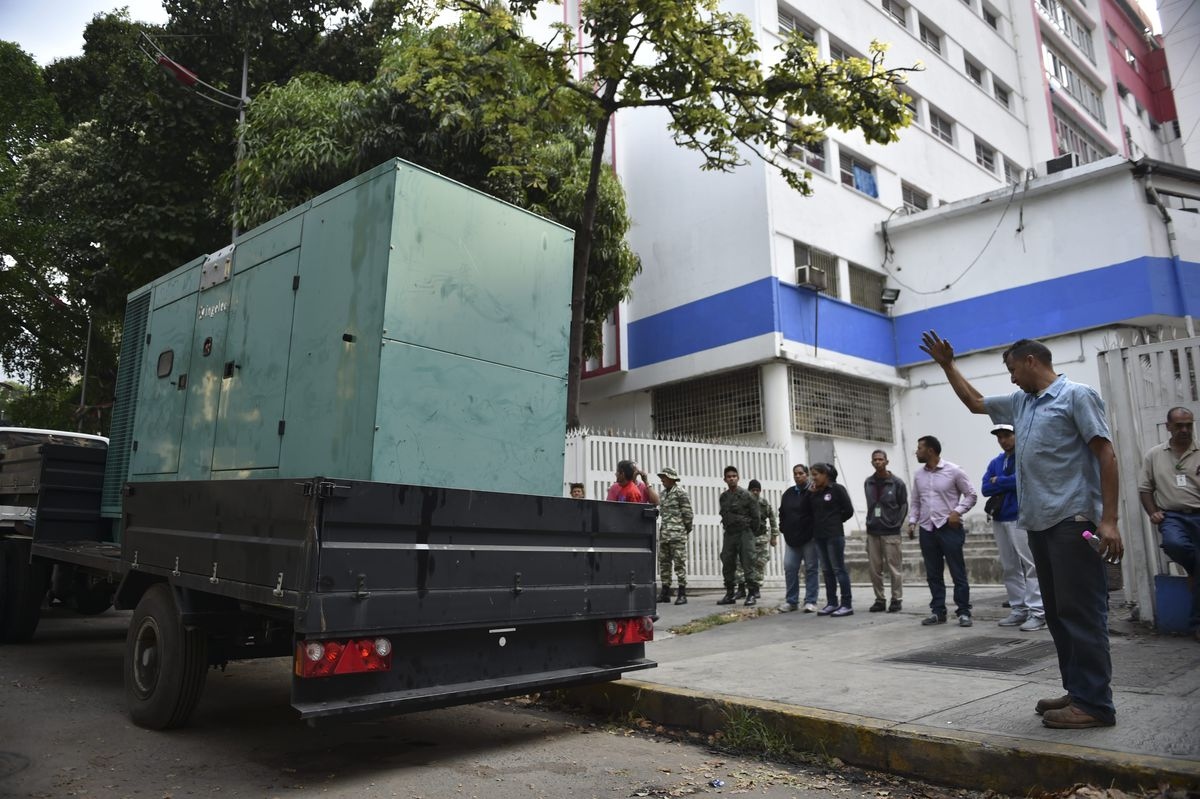 Workers with the state-run electricity company CORPOELEC arrive at a children's hospital with a generator in Caracas on March 8, 2019.