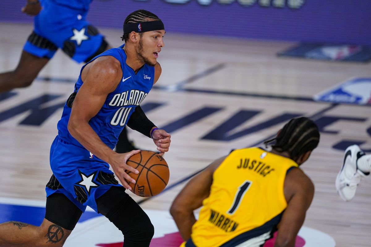 Orlando Magic forward Aaron Gordon brings the ball up court against Indiana Pacers forward T.J. Warren during the second half of an NBA basketball game Tuesday, Aug. 4, 2020 in Lake Buena Vista, Fla.