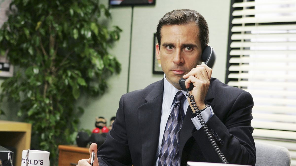 Steve Carell as Michael Scottin The Office, holding a phone to his left ear
