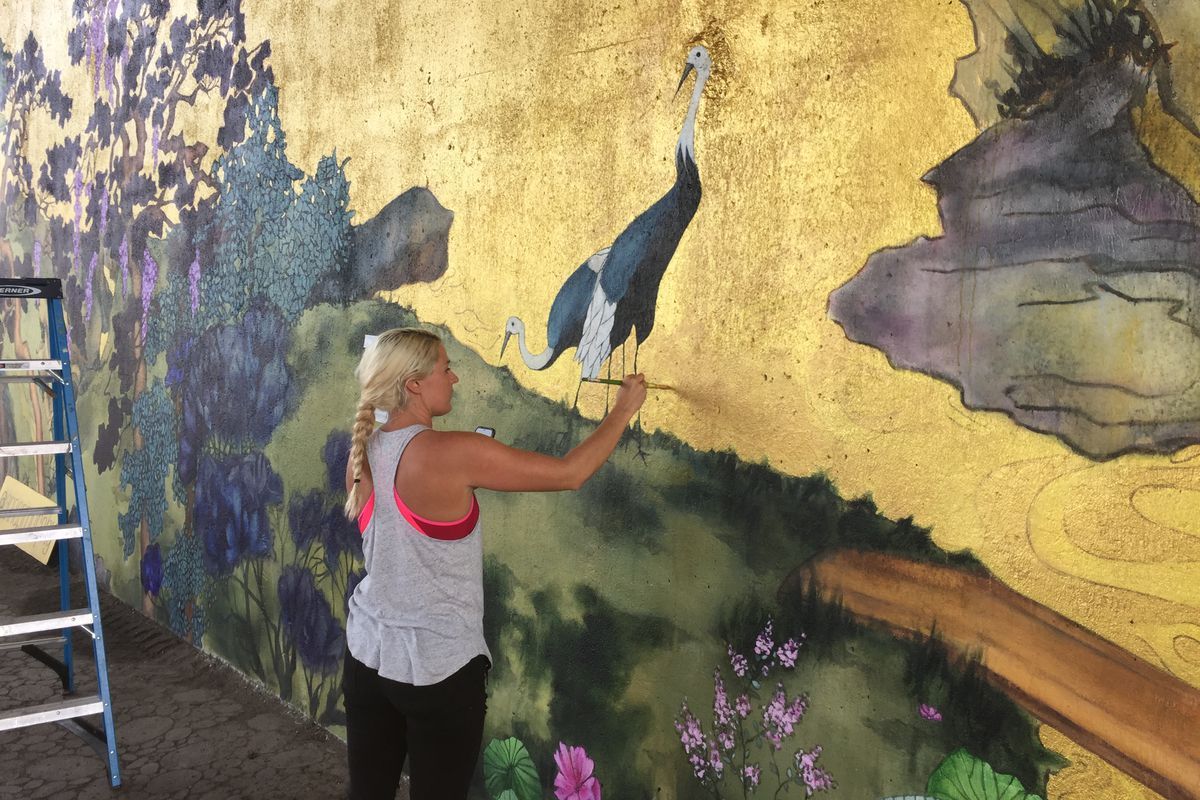 """Anna Murphy works on her new mural, """"Between the Mountains and the Water."""""""