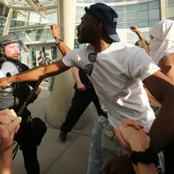 A protester pushes back at a police officer as a large group of people march toward the Public Safety Building in Salt Lake City on Monday, June 1, 2020.