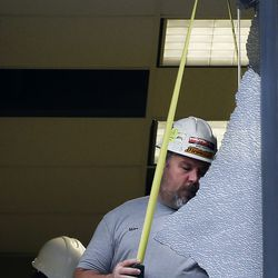 Mike Frampton, of City Glass, measures a broken window at the Maverik Base Camp building on 185 S. State in Salt Lake City after a 5.7 magnitudeearthquakecentered in Magna hit early on Wednesday, March 18, 2020.