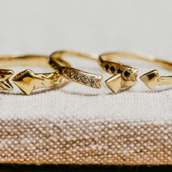 """Versions of the Arrow ring. From left: <a href=""""http://odetteny.com/arrow-ring-brass.html"""">Recycled brass</a> ($75); <a href=""""https://catbirdnyc.com/shop/product.php?productid=19173&cat=0&page=1"""">14k yellow gold with diamonds</a> ($520); and <a href=""""http"""