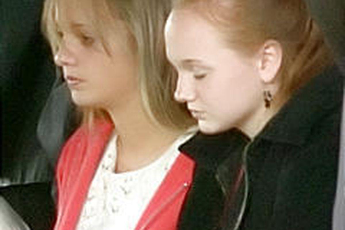 Kara Borden, left, with sister Katelyn at their parents' graveside service. Police say Kara's boyfriend killed her parents.