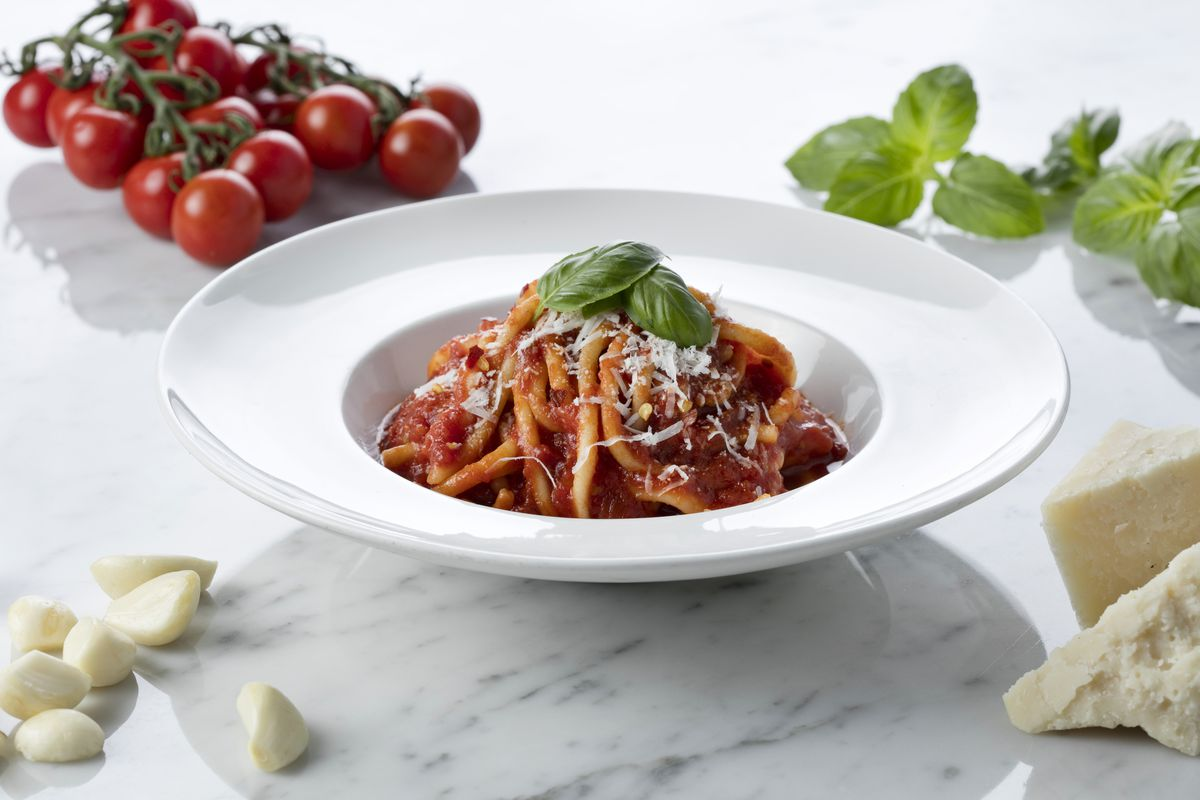 A bowl of bucatini with tomatoes in the background