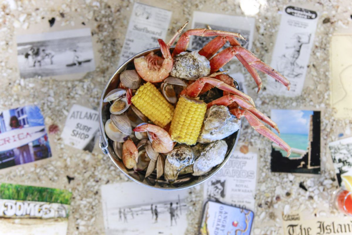 A bucket filled with pieces of corn, crab legs, and shellfish