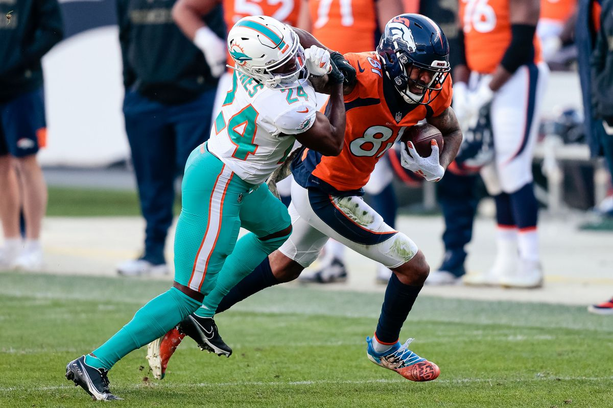 Denver Broncos wide receiver Tim Patrick (81) runs the ball on a reception as Miami Dolphins cornerback Byron Jones (24) defends in the second quarter at Empower Field at Mile High.