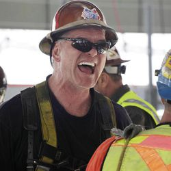 """In this March 23, 2012 photo, an ironworker laughs at the end of his shift at the top of One World Trade Center in New York. One World Trade Center, the giant monolith being built to replace the twin towers destroyed in the Sept. 11 attacks, will lay claim to the title of New York City's tallest skyscraper on Monday, April 30, 2012, as workers erect steel columns that will make its unfinished skeleton a little over 1,250 feet, just high enough to peak over the observation deck on the Empire State Building. The milestone is a preliminary one. The so-called """"Freedom Tower"""" isn't expected to reach its full height for at least another year, at which point it is likely to be declared the tallest building in the U.S."""