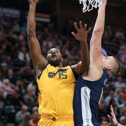 Utah Jazz forward Derrick Favors (15) goes for a layup against Denver Nuggets center Nikola Jokic (15) at Vivint Smart Home Arena in Salt Lake City on Tuesday, Nov. 28, 2017.