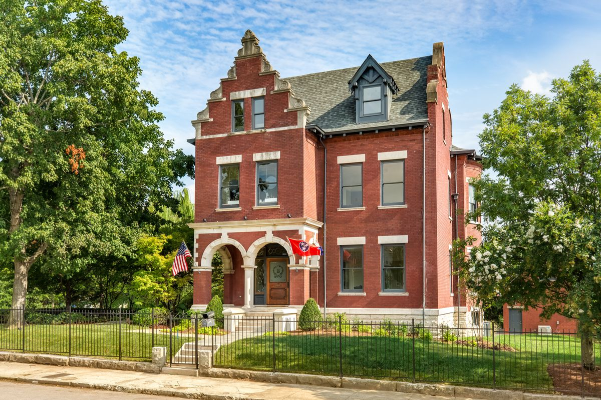 A three-story brick home with ornate, peaked front facade and large windows sits behind metal gate.