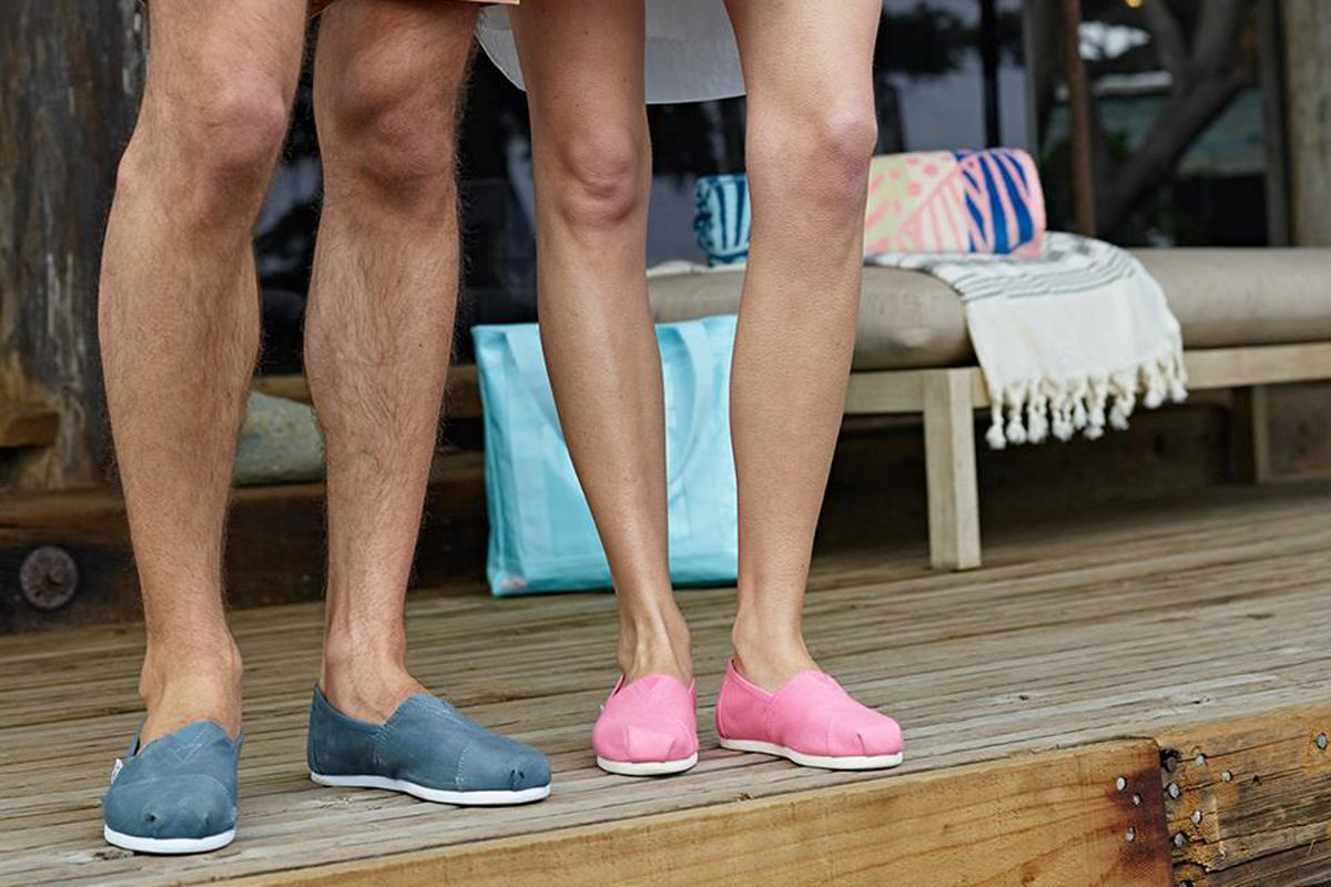 Man and women wearing TOMS shoes on a wooden deck