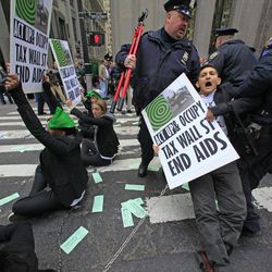 Police arrest members of a combined group of ACT UP and Occupy Wall Street activists who chained themselves, blocking traffic, at Wall Street and Broadway, near the New York Stock Exchange, on Wednesday, April 25, 2012, in New York.