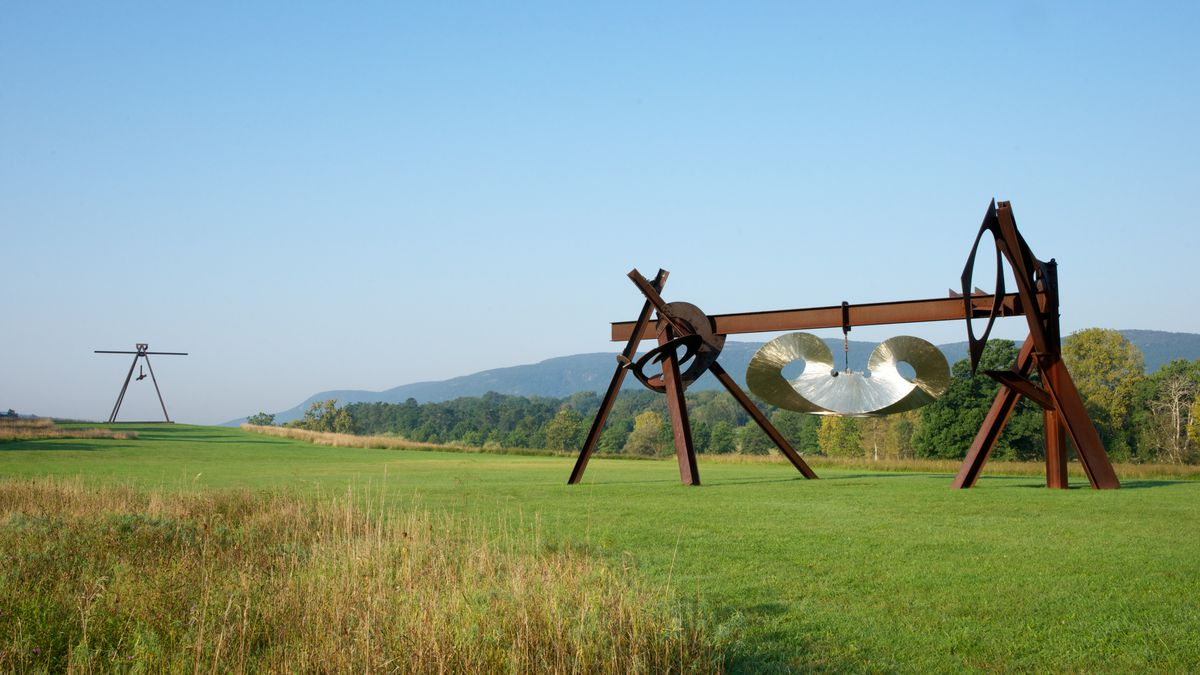 A sculpture sits on a green lawn. In the distance are trees and mountains.
