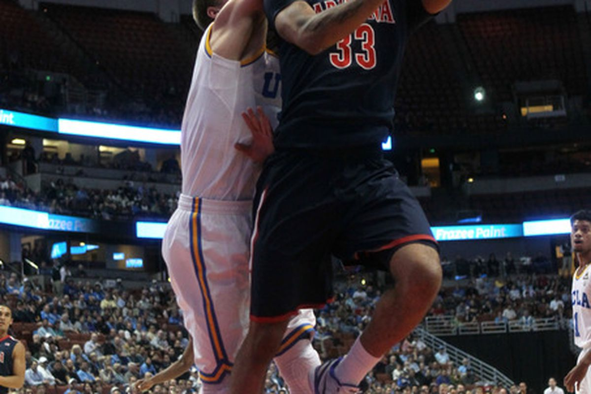ANAHEIM, CA - JANUARY 05:  Jesse Perry #33 of the Arizona Wildcats shoots over David Wear #12 of the UCLA Bruins at the Honda Center on January 5, 2012 in Anaheim, California.  (Photo by Stephen Dunn/Getty Images)