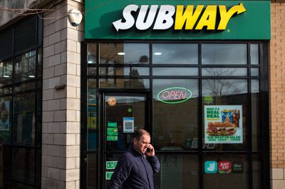 A man passing a Subway restaurant in London. Latest Covid-19...