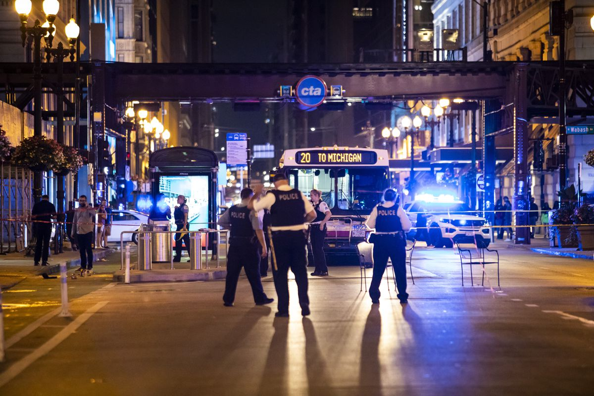 Chicago police investigate Saturday night in the first block of East Washington Avenue in the Loop, where a CTA bus driver was physically attacked and then shot.