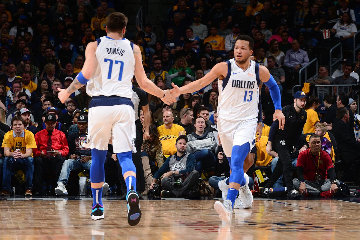 Luka Doncic and Jalen Brunson of the Dallas Mavericks high five during the game against the Denver Nuggets on March 14, 2019 at the Pepsi Center in Denver, Colorado.