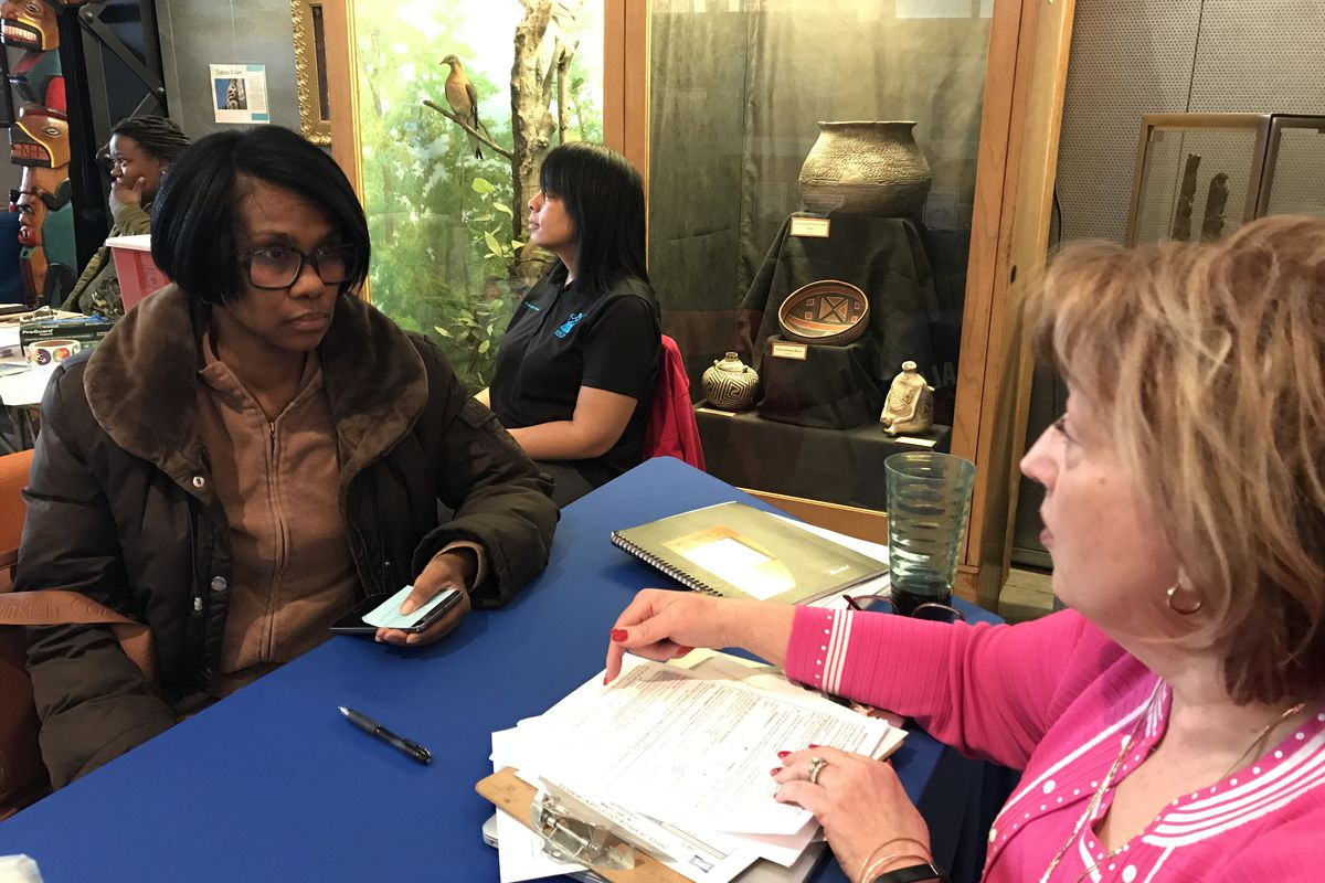 April Thomas enrolls her son with Deborah Louis-Ake, who leads the main district's special education placement at the Children's  Museum in Detroit.