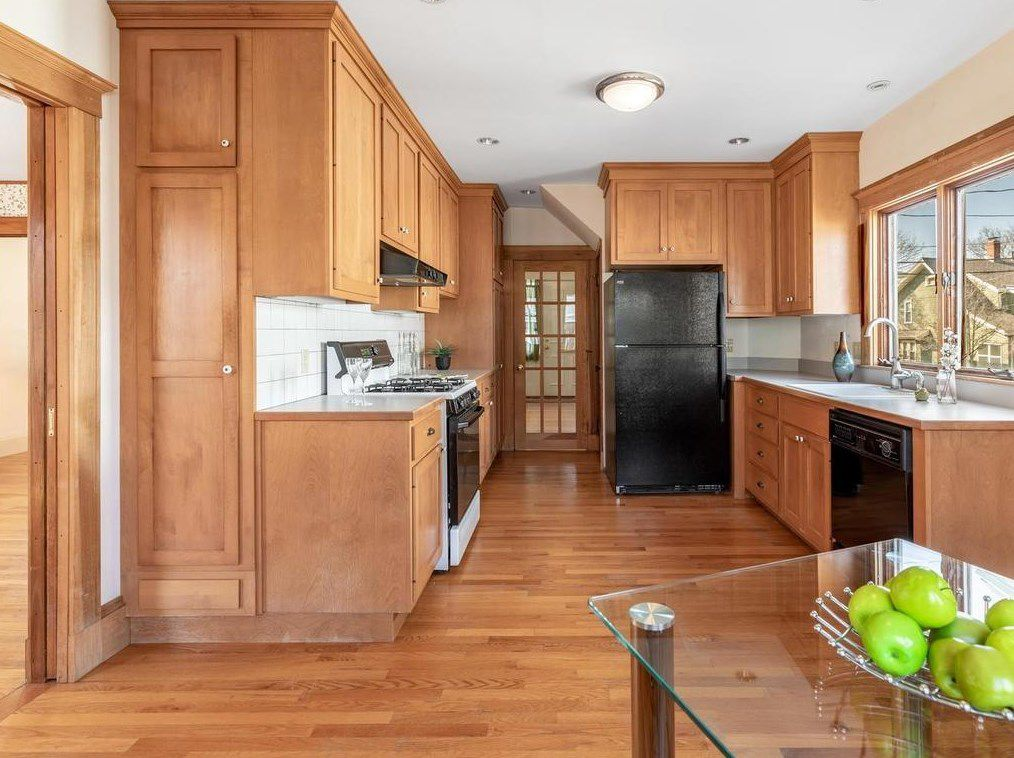 The long view of a kitchen with cabinetry and counters, and there's a table in the foreground.