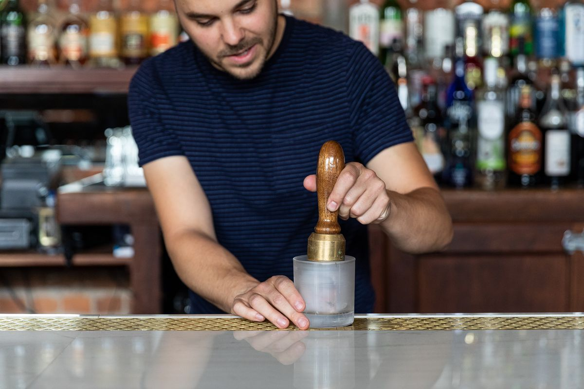 Wilson wears a blue and black striped T-shirt and stands behind the bar holding a frosted glass and a wood and brass stamping tool.