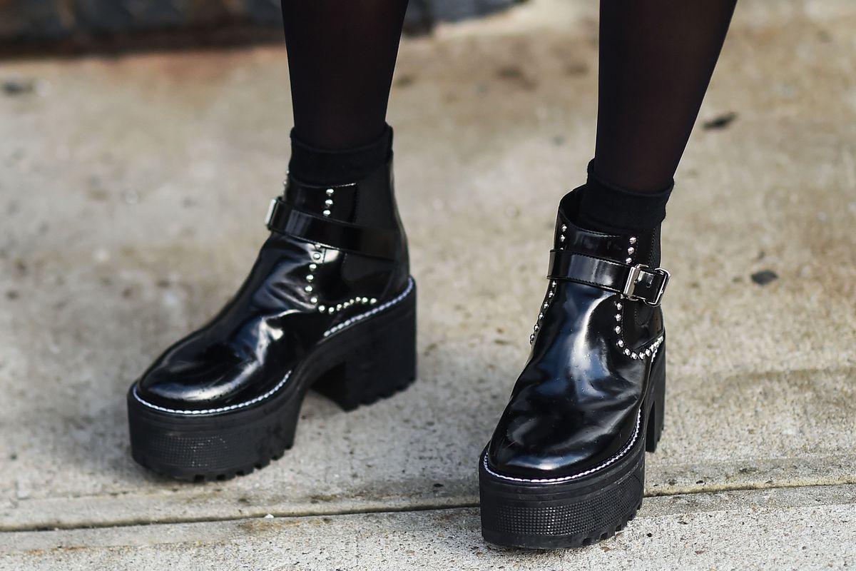 Feet wearing black platform shoes