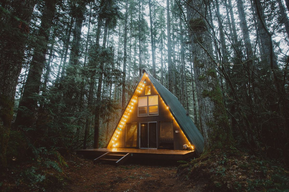 The exterior of an A-frame house in a forest in Washington. The house has a deck and a painted black roof. There are lights running along the frame of the house. The house is surrounded by trees.