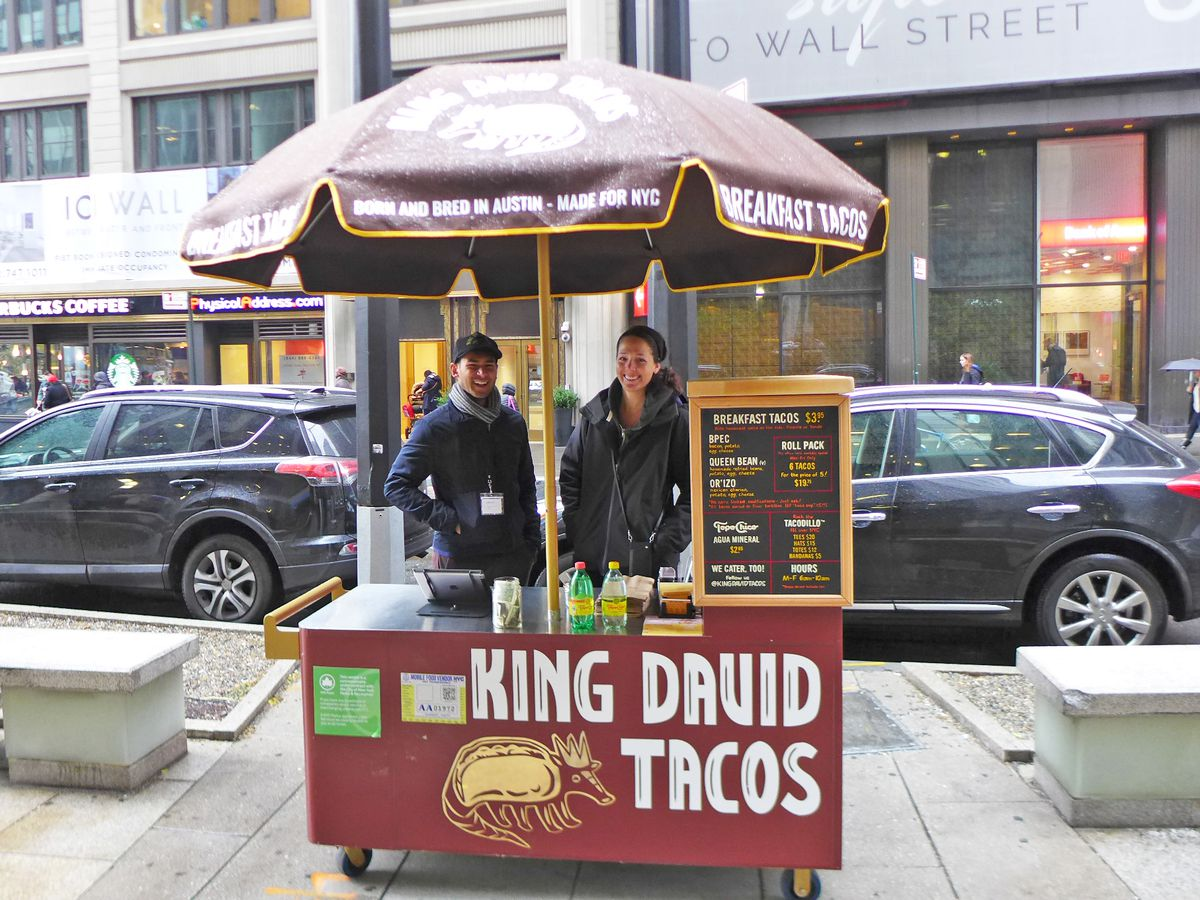 """Two people stand under an umbrella at a small red food cart, whose sign reads """"King David Tacos"""" in capital letters"""