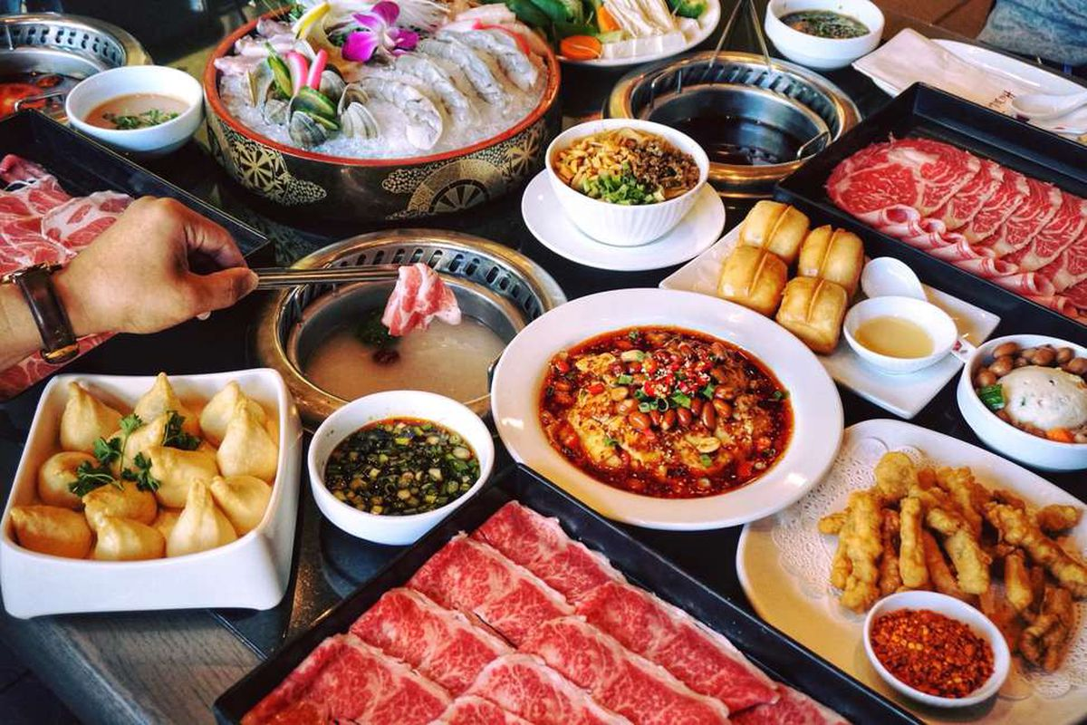 A hand dips a meat in a broth at a hot pot restaurant, with several dishes surrounding the bowl, including plates of raw meat, dumplings, and shrimp.