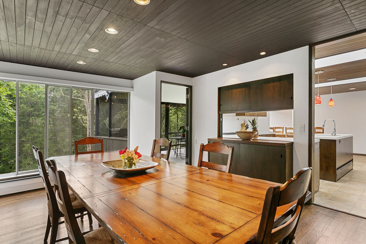 A wooden dining room table and chairs sits in front of windows and next to a kitchen.
