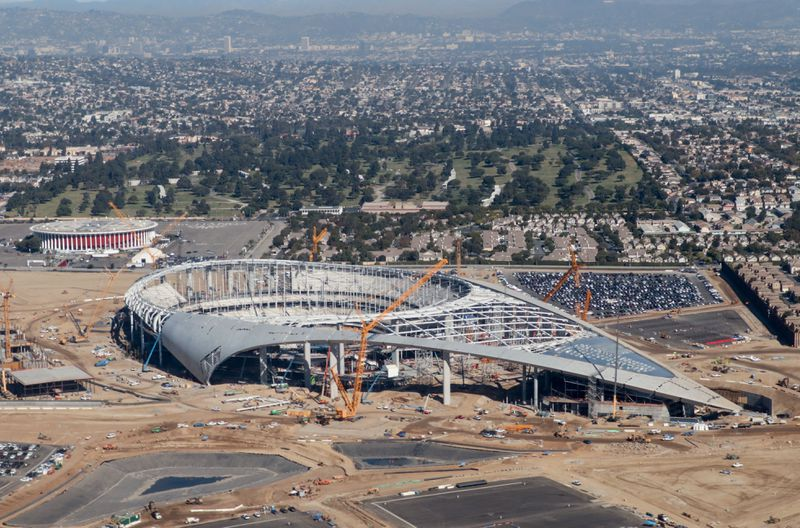 An aerial photo of the in-progress stadium, with cranes around it and the shell of the roof showing less progress than it does in current photos.