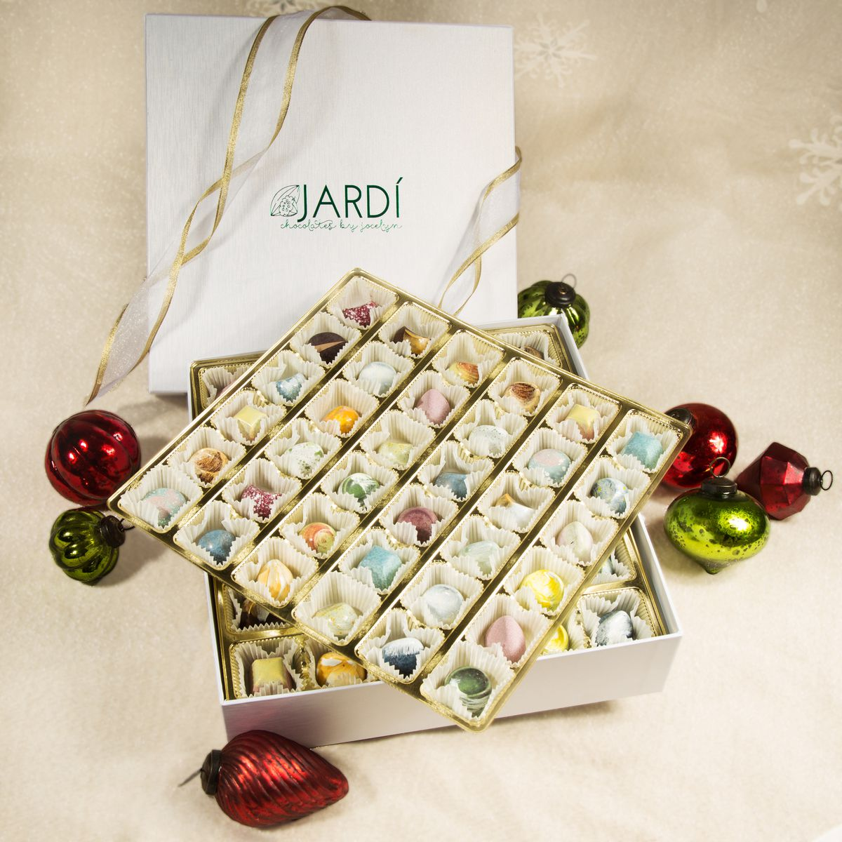 Box of 72 chocolates with seven red and green christmas ornaments around it