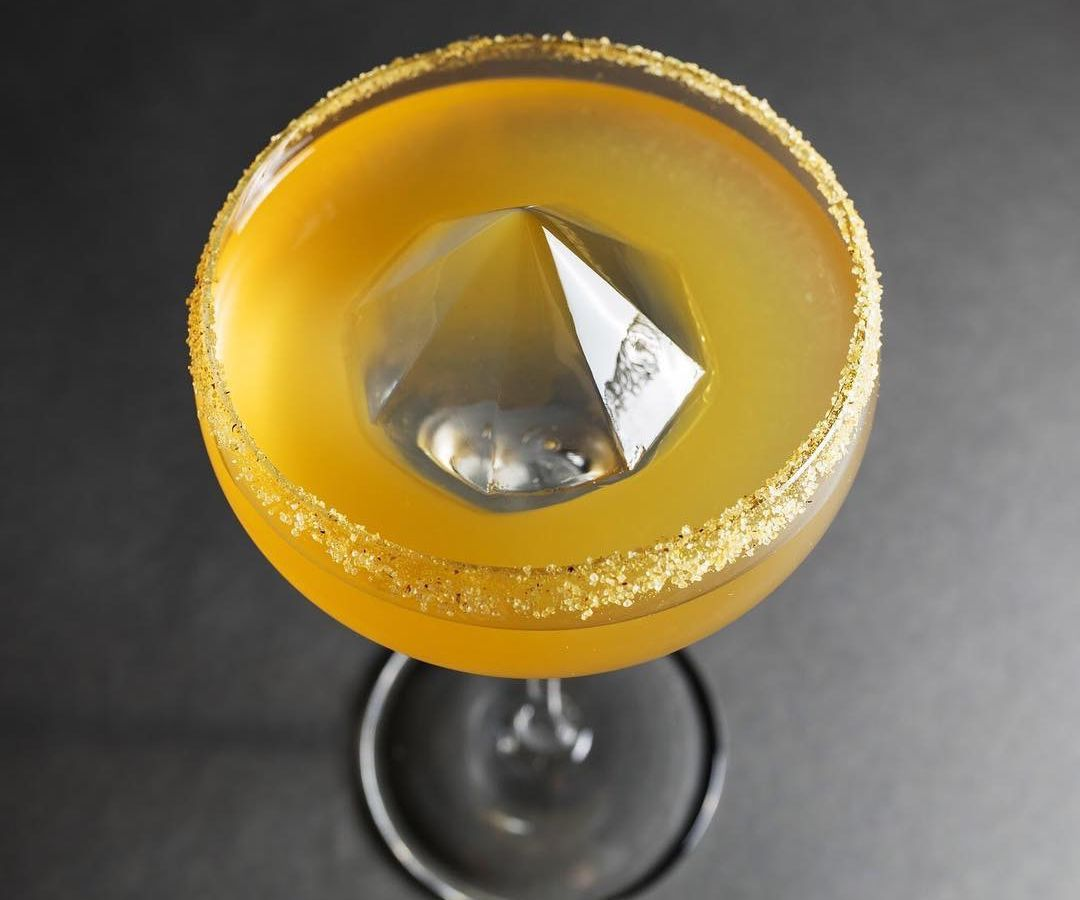 From above, a gold cocktail in a coupe with a diamond shaped piece of ice rising from the center and gold dust around the rim, sitting on a blank gray surface