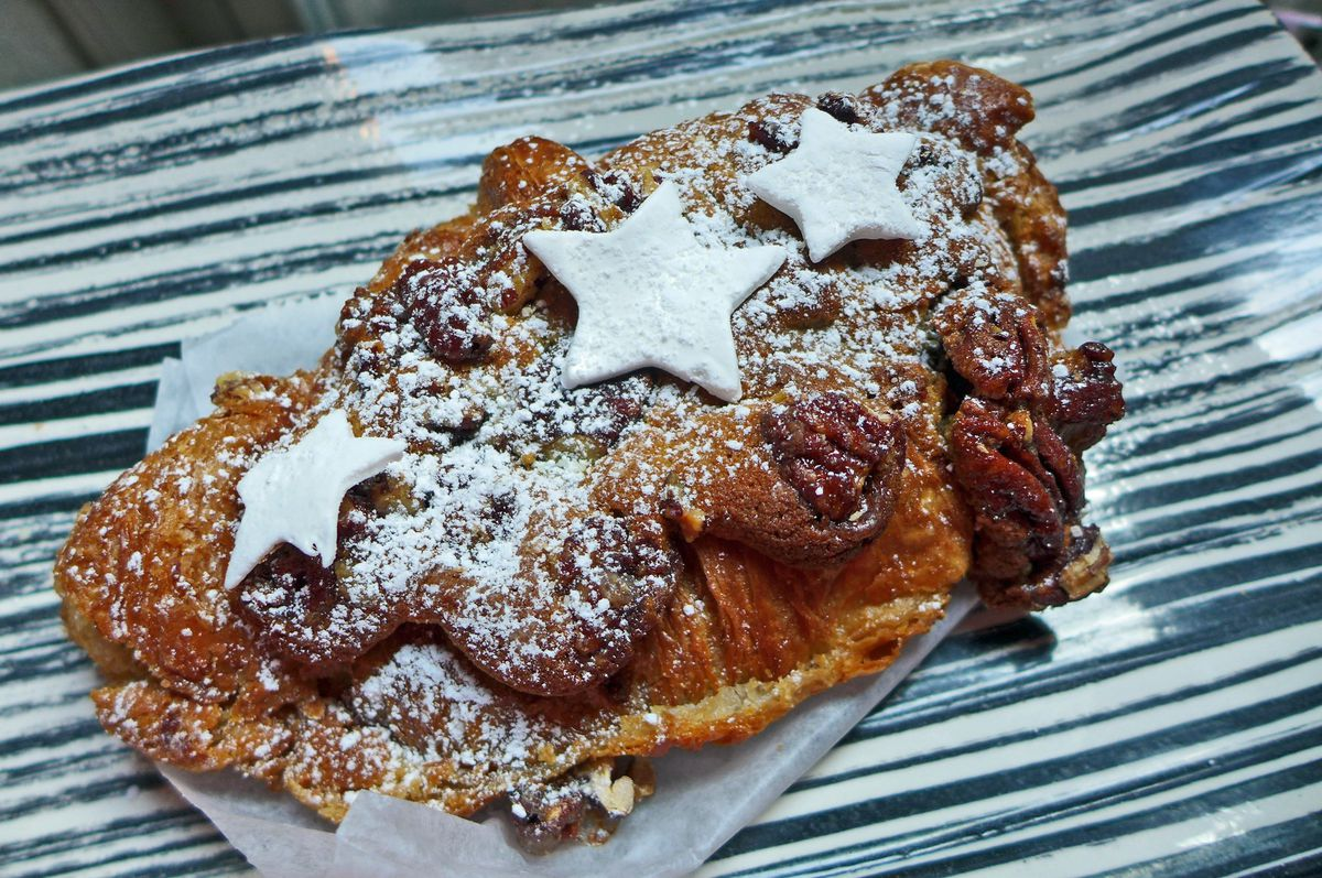 A croissant covered in powdered sugar and star-shaped marshmallows