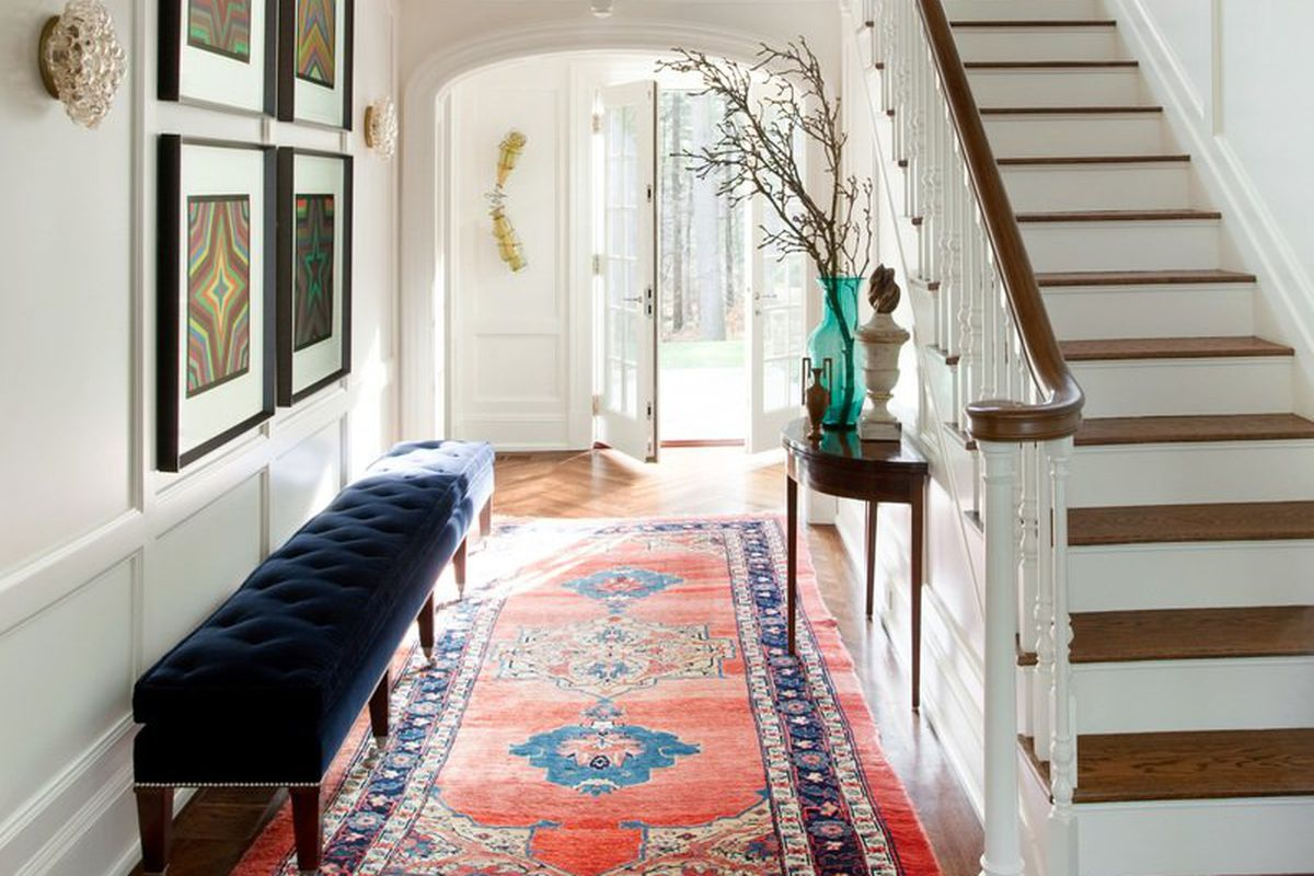 An interior of a house entryway with stairs on the right leading up and a patterned carpet in the hall leading from the front door