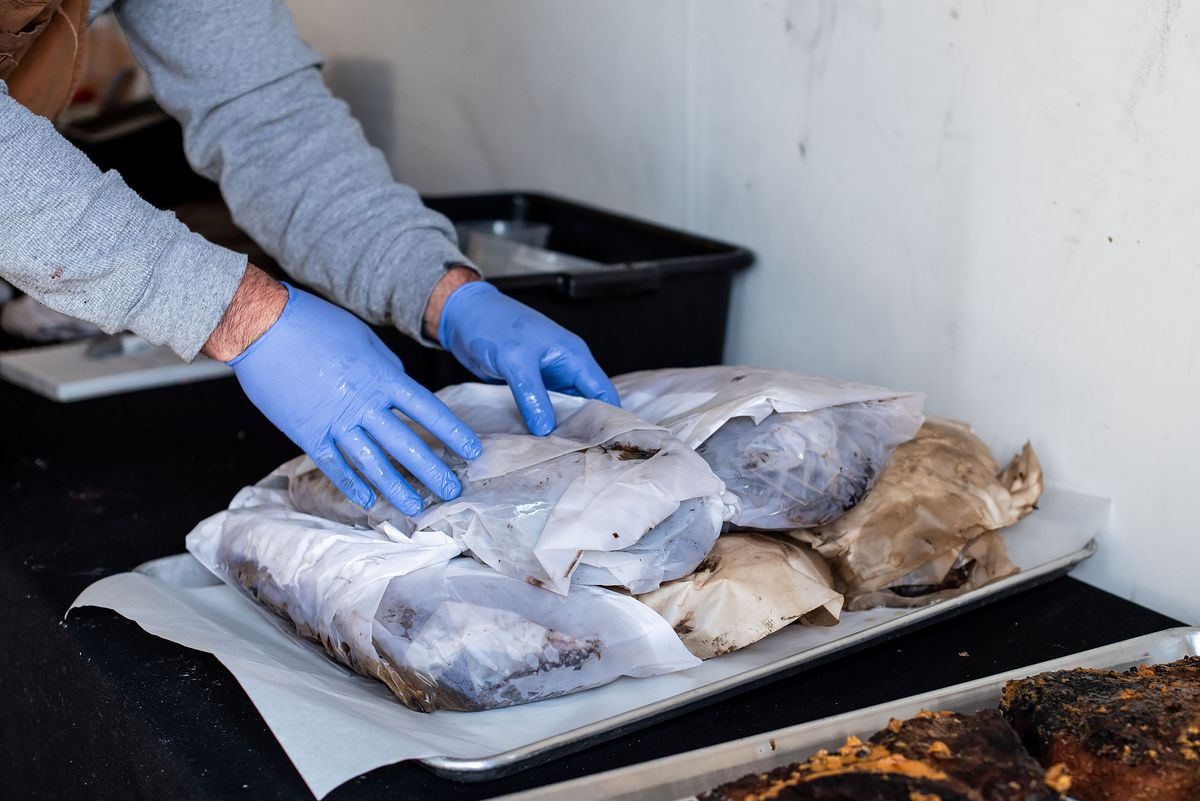Wrapped smoked meats, including brisket, being picked up by hands wearing blue gloves.