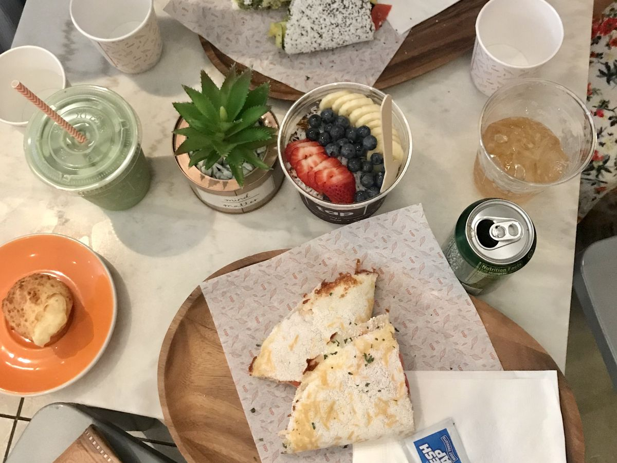 An overhead shot of a spread of food including a tapioca crepe and acai bowl