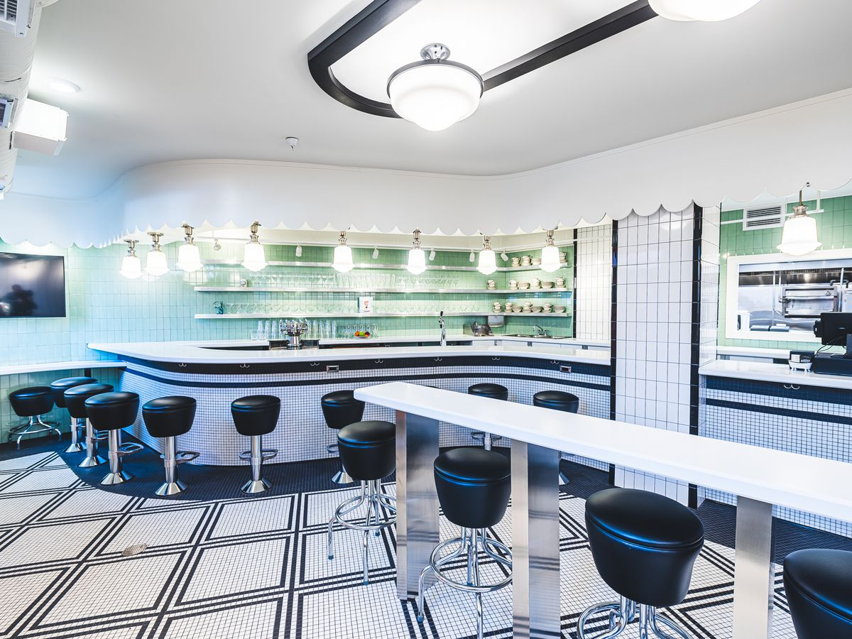 The interior of the new Buffalo & Bergen is covered in black and white tiles, black barstools, and a mint green backsplash that completes a minimalist, retro style.