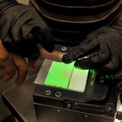 An illegal immigrant is fingerprinted as part of processing in order to create or update a file on that immigrant at Tucson Sector U.S. Border Patrol Headquarters Thursday, Aug. 9, 2012, in Tucson, Ariz.  The U.S. government has halted flights home for Mexicans caught entering the country illegally in the deadly summer heat of Arizona's deserts, a money-saving move that ends a seven-year experiment that cost taxpayers nearly $100 million.