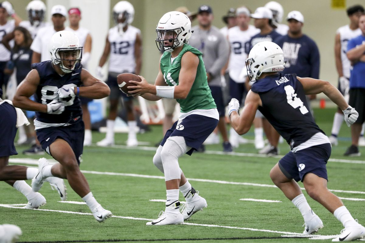 BYU quarterback Zach Wilson runs a play during football practice in Provo on Friday, Aug. 3, 2018.