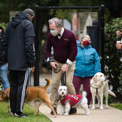 Robert Kosticak, center, and his pet Blanco interact with attendees of a pet blessing ceremony in celebration of the feast day of St. Francis of Assisi.