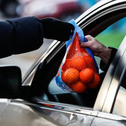 Brandi Jolley hands a bag of oranges to a recipient during the Big Brother Big Sister's Holiday Drive Thru at a parking lot in Taylorsville on Thursday, Dec. 10, 2020.During the event, Littles (youths living in adversity), their Bigs (volunteer mentors) and their families were invited to pick up warm winter coats, gift cards and fun treats.