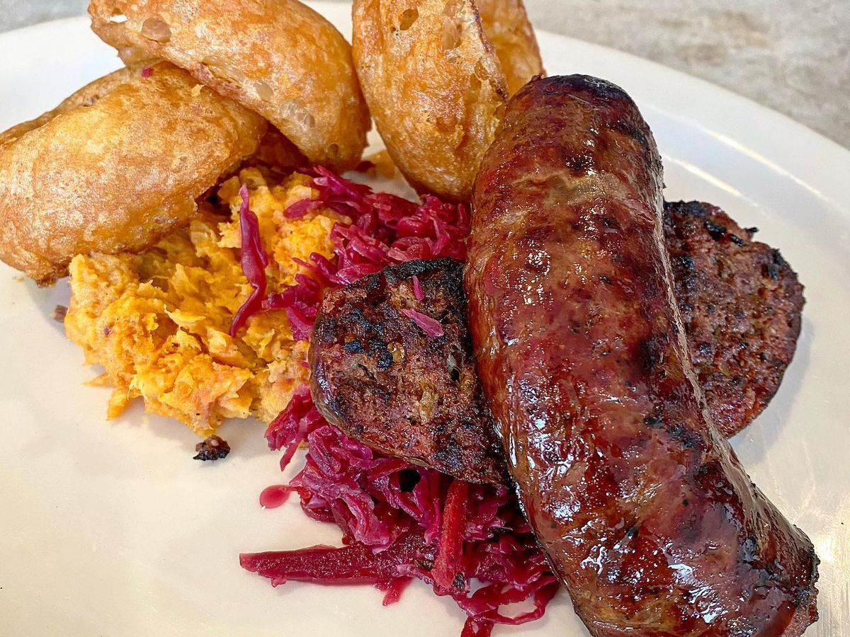 Antelope sausage with red cabbage and sweet potatoes and fried onion rings on a white plate