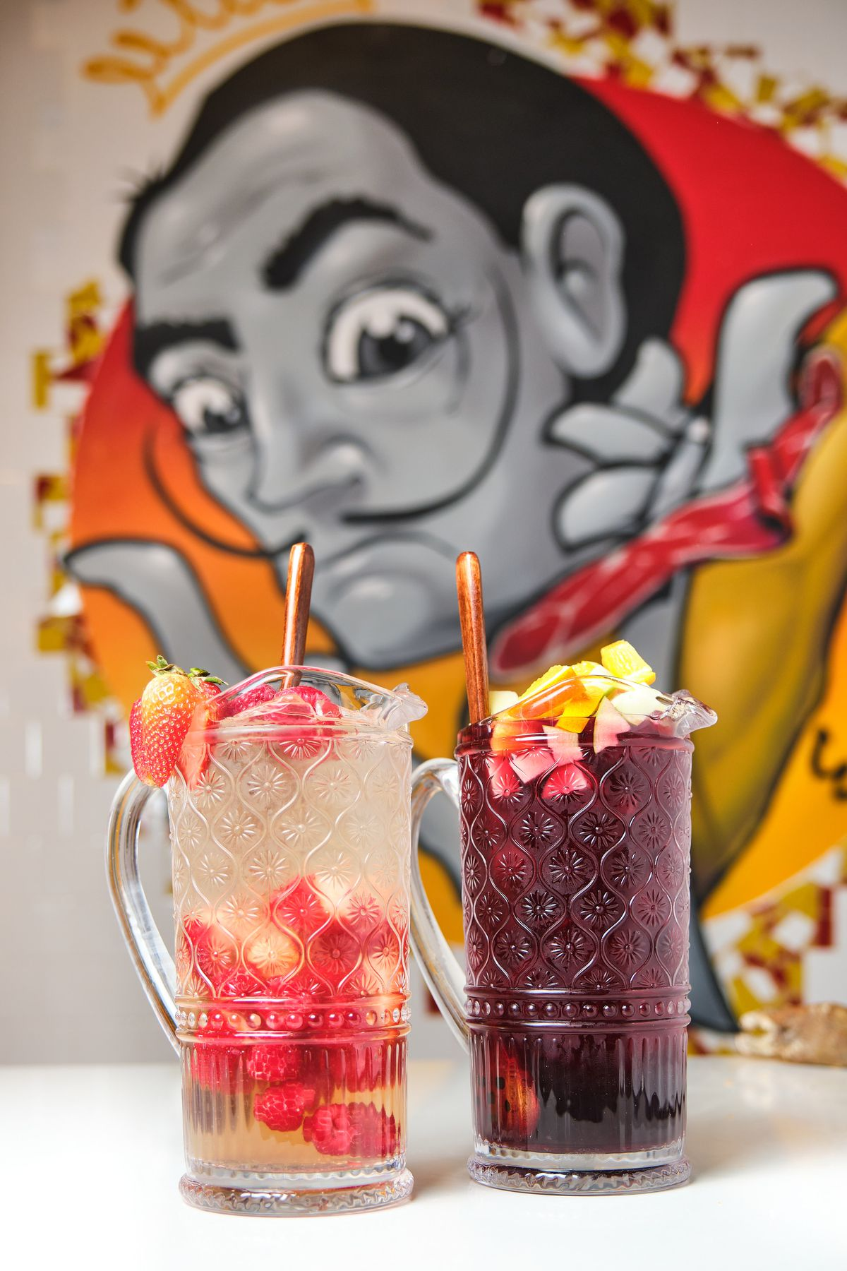 A mural of Salvador Dalí with two cocktails in front of it