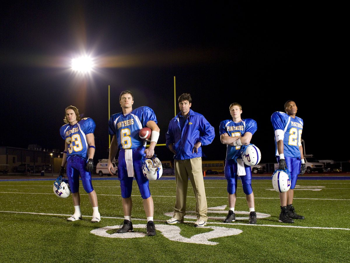 Still with coach and four football players in blue uniforms on lighted field at night