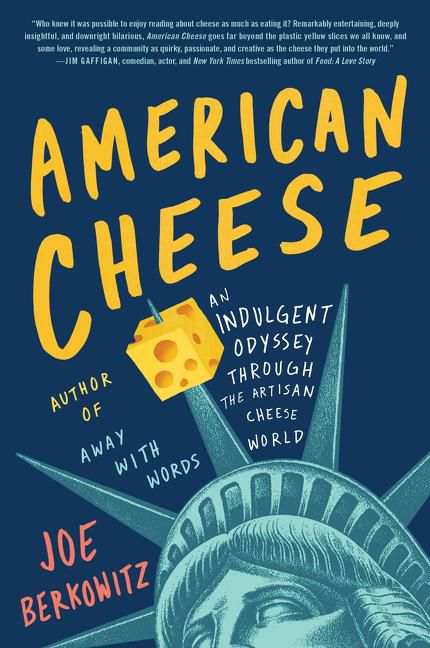 The cover of a book called American Cheese, featuring yellow text on a blue background, and the head of the statue of liberty with a piece of cheese stuck to one of the crown prongs