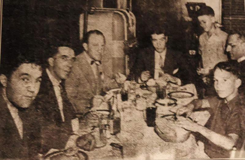 """Young Larry Panozzo (front right) enjoys a spaghetti dinner with New York Yankees legend Joe DiMaggio (rear, center) at St. Anthony of Padua parish in the early 1940s. Also present (from left): his uncle Louis Panozzo, then-Ald. Dominic Lupo, Oscar """"Ski"""" Melillo, who played for the St. Louis Browns and Boston Red Sox and (behind Larry) the Rev. Joseph Chiminello."""