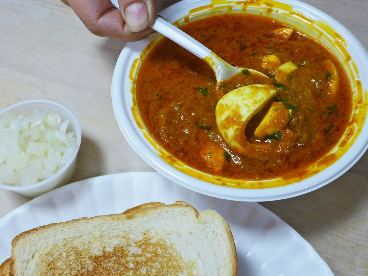 A hand holds up a fragment of boiled egg on a plastic spoon over a bowl of red sauce.