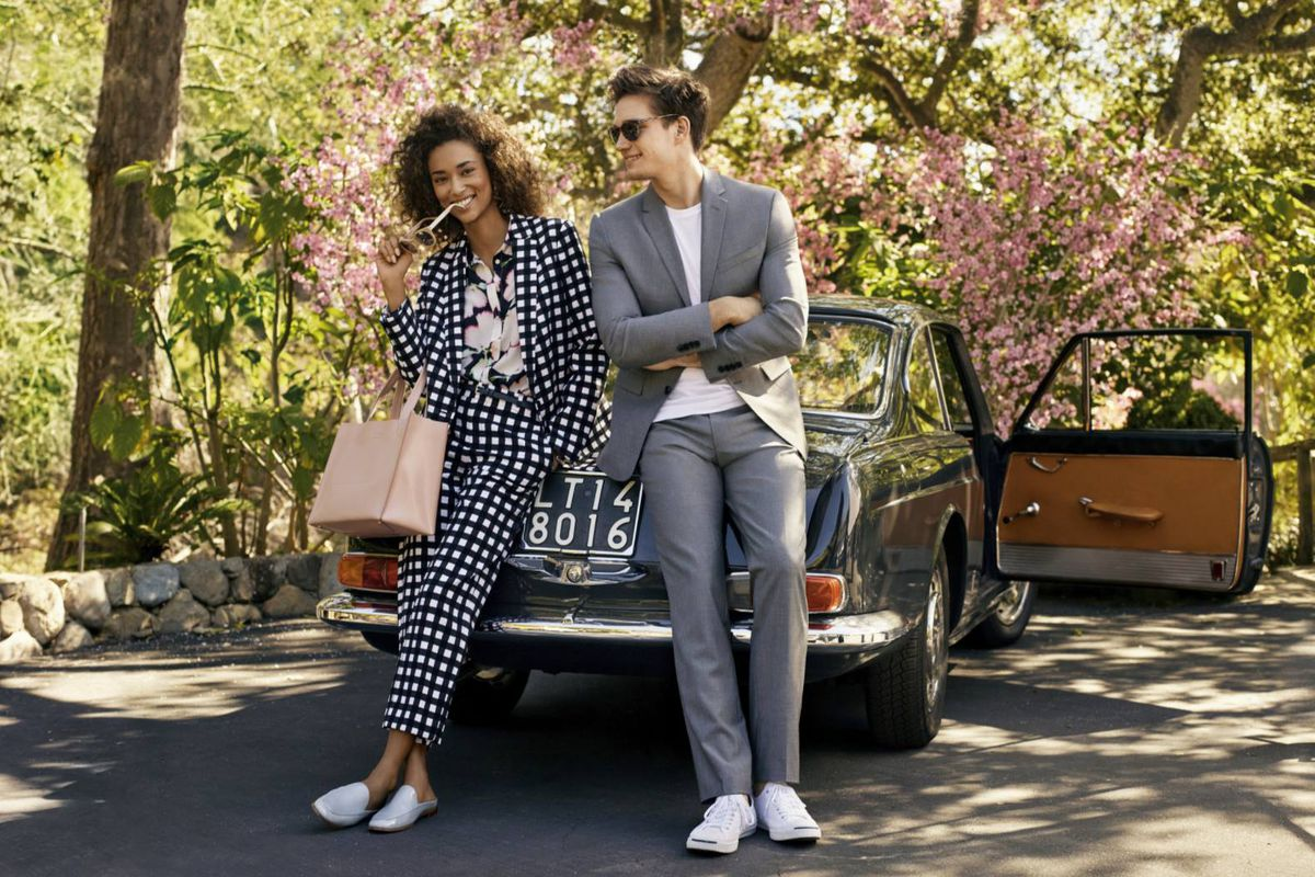 Two models wearing Banana Republic clothes, leaning on an old car in the woods